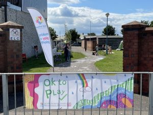 """A colourful banner with words """"ok to play"""" hung on railings in front of apark."""