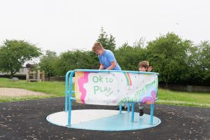 In a playpark, on a roundabout hangs a banners with the words of to play. A young boy is being pushed on the roundabout by a man, both are smiling.