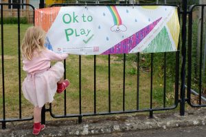 A banner on railings reads Ok to Play. A young girl plays at climbing the railings next to it.