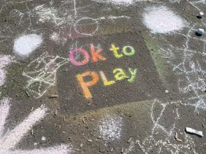 the words Ok to Play are stenciled in rainbow colours on a pavement.